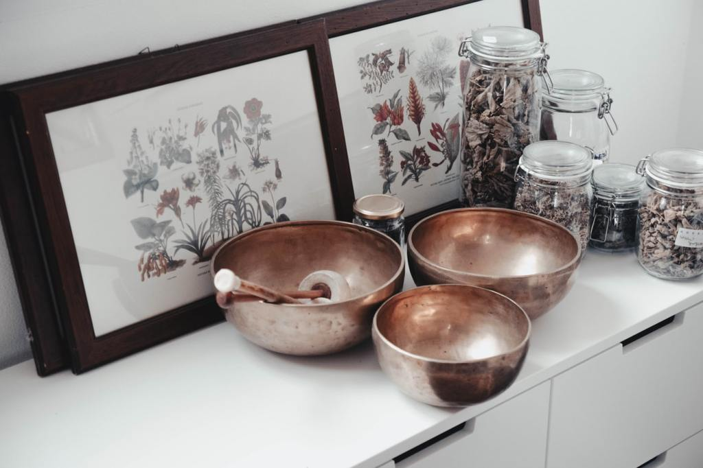 A still-life photograph showing copper bowls, dried herbs in glass containers, and framed pictures of drawings of various plants and herbs.